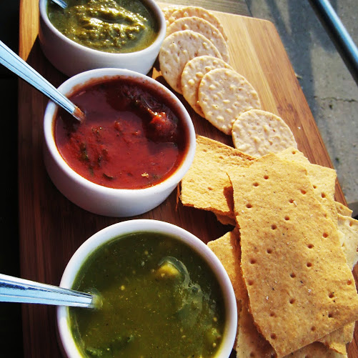 Tomatillo pistachio salsa, tomato hibiscus ghost pepper salsa, and avocado salsa verde, served with masa and rice crackers