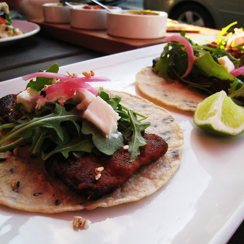 Pork belly tacos with sesame tortilla, morita salsa, fresh mozzarella, pickled onions, and arugula