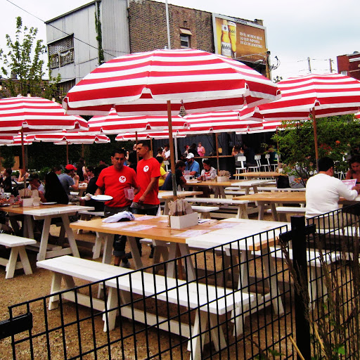Striped umbrellas & picnic tables on the spacious patio