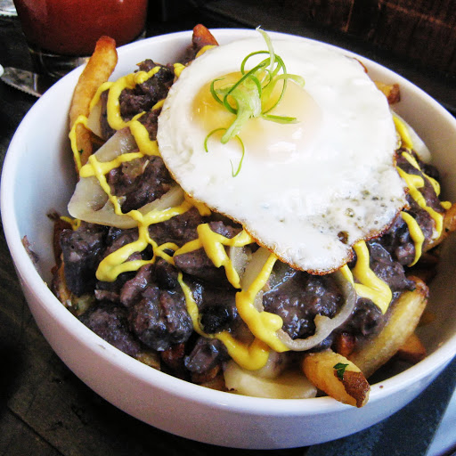 Feijoada fries with black beans, provolone, pickled fresnos, green onions, sour cream and mustard sauce, and fried egg